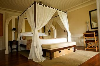 tropical four poster canopy with sheer white curtains