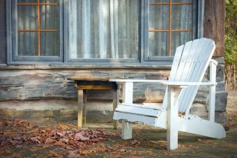 A white adirondack chair on a wooden deck