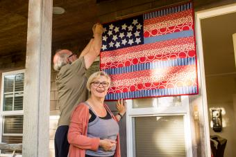 Couple hanging American flag quilt
