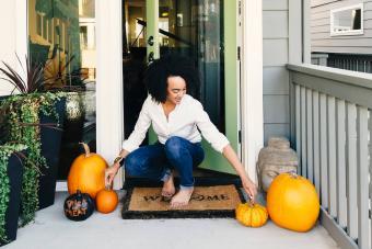 woman arranging pumpkins on patio