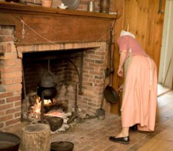 Woman using colonial fireplace for cooking