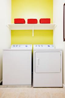 washer and dryer with shelf above them