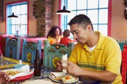 Man Eating In Mexican Restaurant