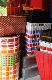Colorful wicker and straw trash baskets.