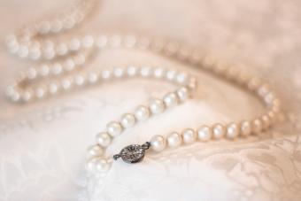 Vintage pearl necklace on floral satin fabric