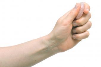 Hand holding a rose quartz worry stone