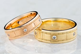 Pair of modern textured wedding rings decorated with diamonds