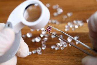 Jeweler checking gem for identity