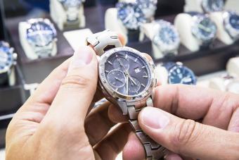 Mens wristwatch being held in a watch shop