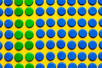 Pattern of many blue and green metal bottle caps on yellow