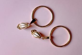 Vintage golden clip-on earrings on pink background