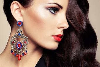 woman in black dress with colorful earrings