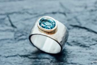 Silver ring with Topaz in gold setting on slate