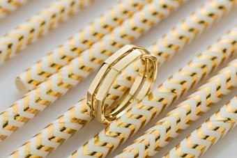 Geometric shape gold ring on golden glossy background
