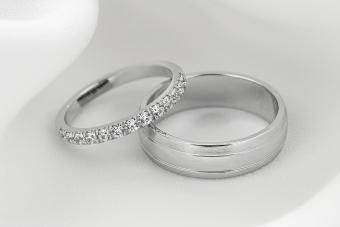 Pair of modern white gold wedding ring bands with diamonds on female ring.
