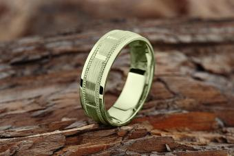 Modern green gold textured wedding ring on natural wood background