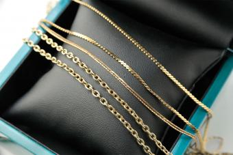 three assorted gold necklaces lay over a jewelry box
