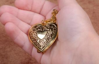 Girl holding heart locket in hand
