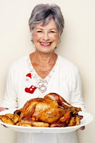 Senior woman holding roast turkey on serving plate