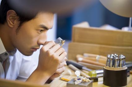Male jeweller examining jewellery with loupe