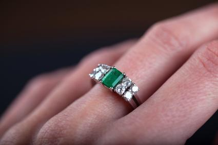emerald ring in woman finger, with diamonds and platinum