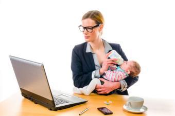 businesswoman feeding her baby