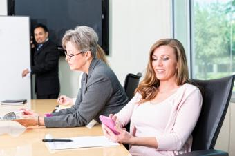 Woman on Cell Phone During Business Meeting