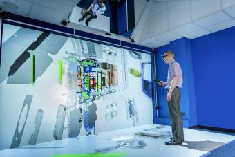 Engineer looking at component parts of machine in 3D in virtual reality suite