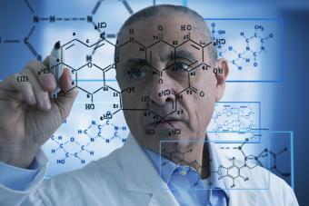 Scientist writing formula on glass wall
