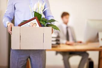 Man leaving with a box of his possessions after being fired