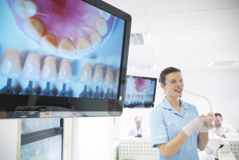 Dentist wearing safety glasses and holding dental equipment next to screens showing images of teeth