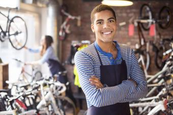 Bike shop teen worker stands proudly in front of his stock