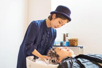 Teen hairdresser shampooing a woman