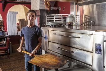 Teenage boy holding spatula in pizza restaurant