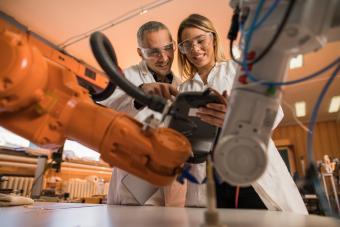 Robotic engineers working on industrial robotic arm