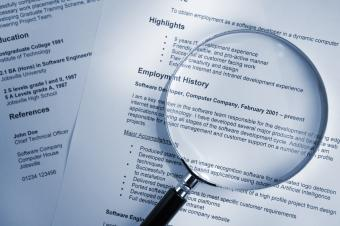 Examining resume employment history with magnifying glass