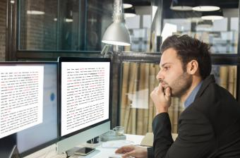 Writer looking at manuscript on monitors
