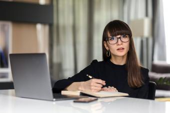 Businesswoman With Laptop Sitting At Office Desk