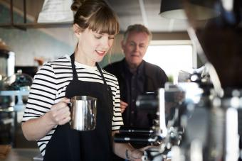Female barista making coffee with customer standing in background at cafe