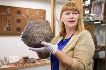 Historian holding artifact in museum