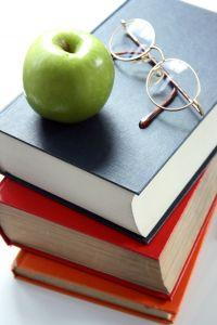 Ready glasses, an apple, and books to study
