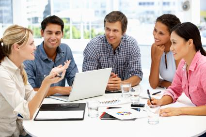 Group of 5 smiling people at a business meeting
