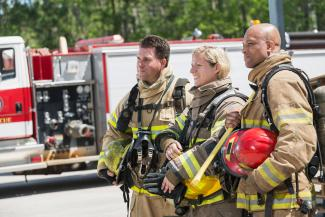 Female firefighter with two male colleagues