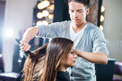 Hairdresser combing woman's hair