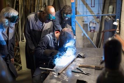 Metal workers being shown welding