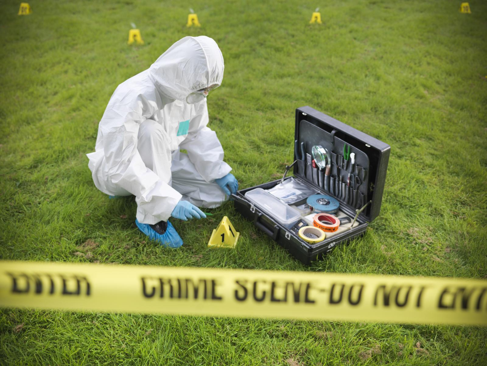 Forensic scientist inspecting toolkit at crime scene