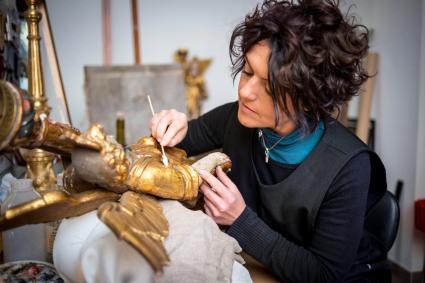 Restorer and framer laboratory craftswomen: Restoring antique golden angel statue