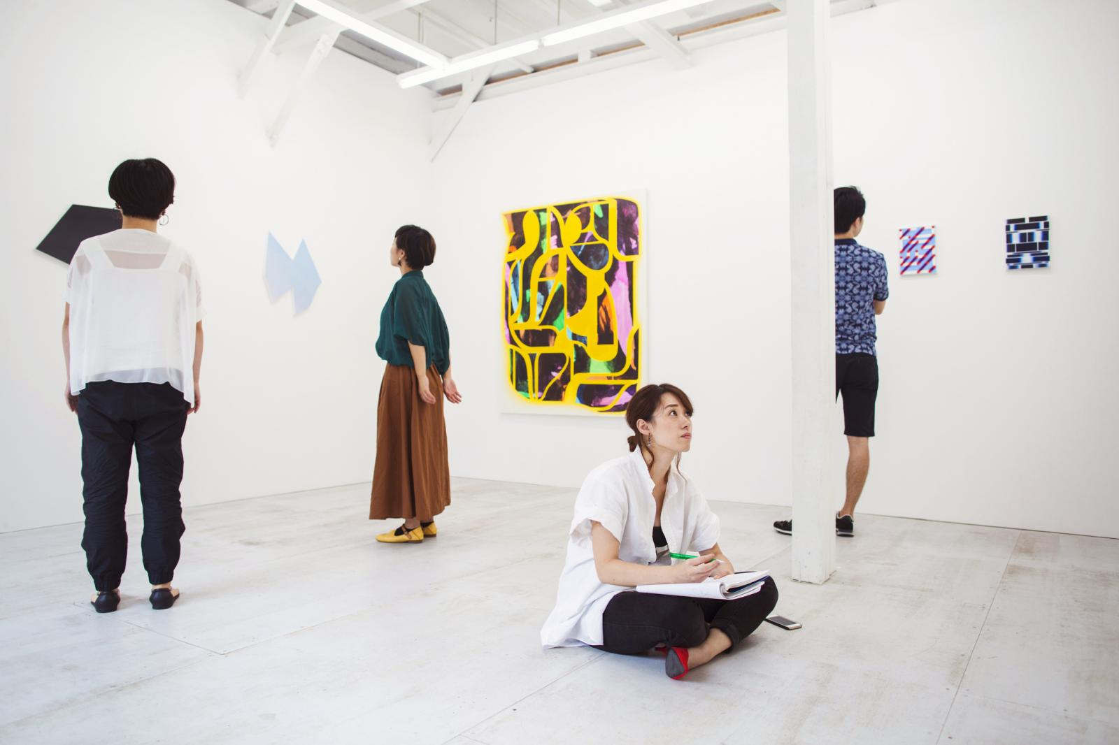 Woman sitting on floor in art gallery with pen and paper, looking at modern painting