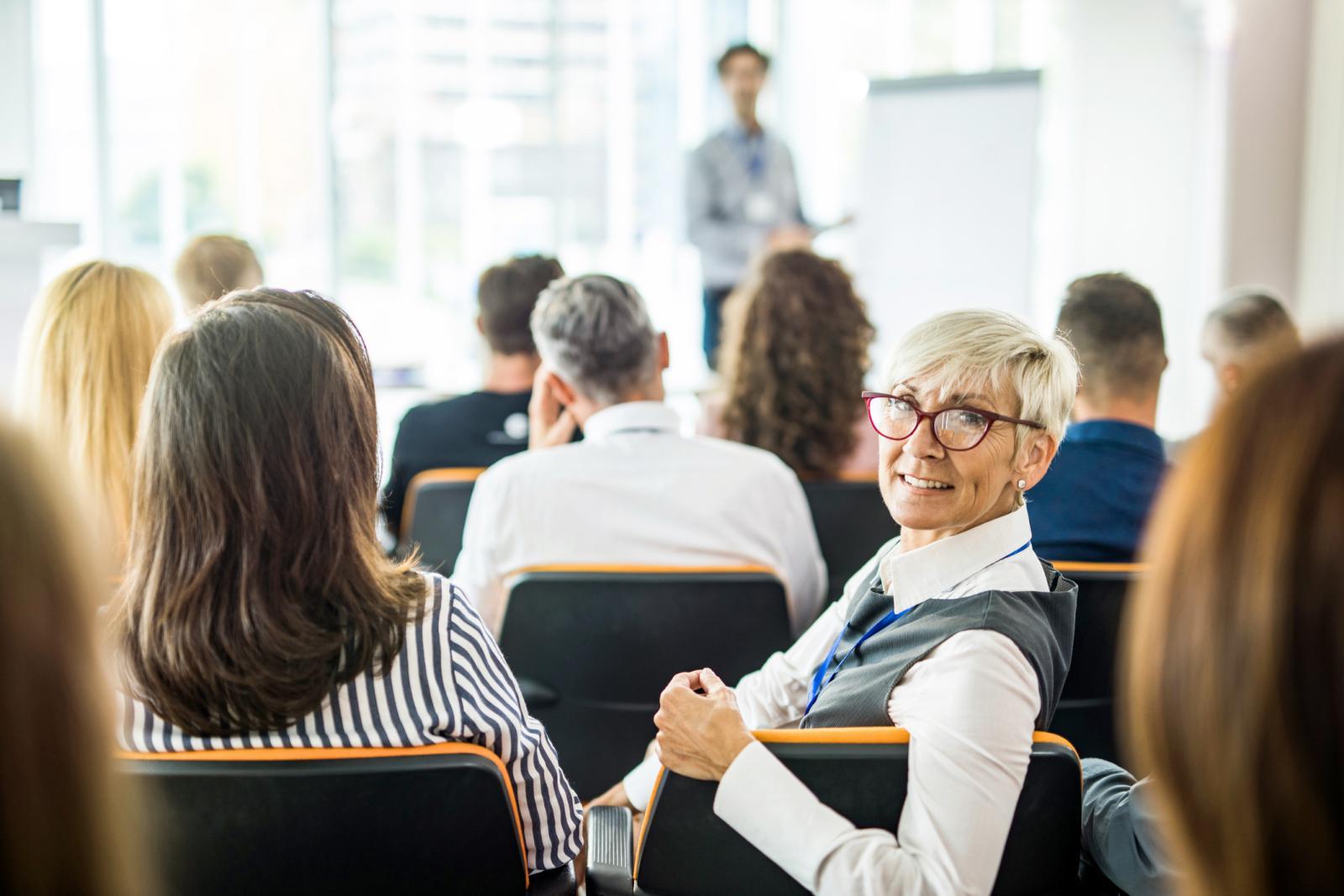 Happy senior businesswoman on a seminar in a board room