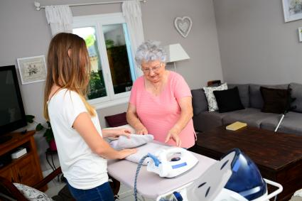 Young girl ironing and helping elderly woman at home